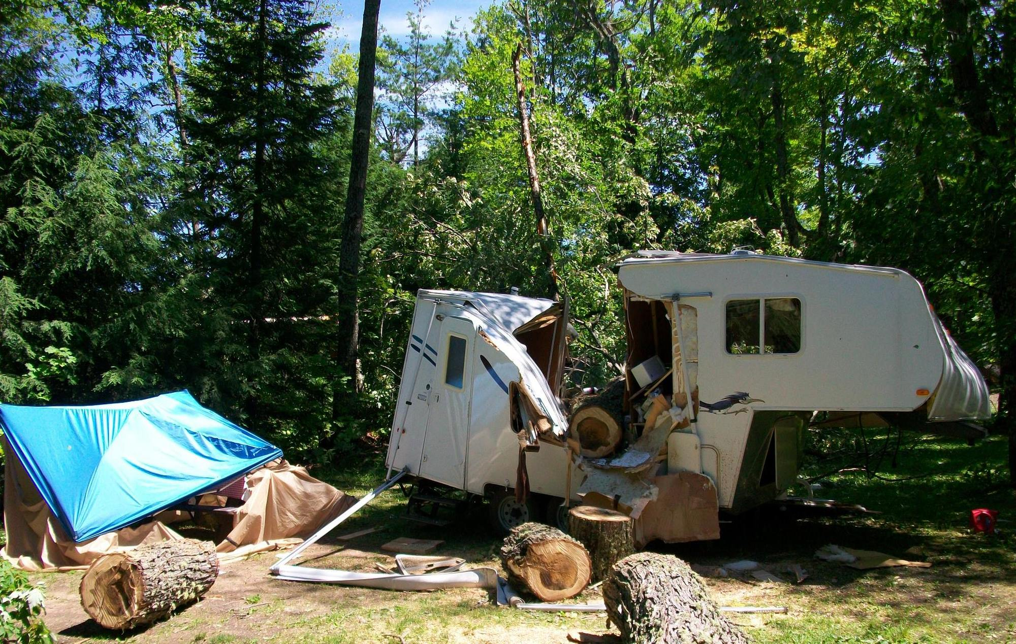 Tree fall storm damage to one of two travel campers at the Emily Lake State Forest Campground in Houghton County. No injuries were reported.