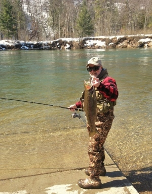 Fisherman in waders holding fishing pole and steelhead