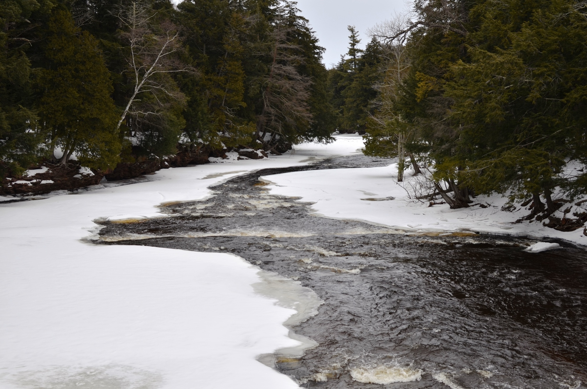The Presque Isle River flows through a wintry landscape toward its mouth at Lake Superior at Porcupine Mountains Wilderness State Park.