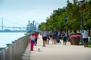 large group of people walking on trail beside Detroit River
