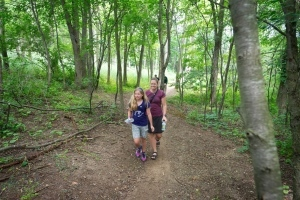 mother and daughter hiking on wooded trail
