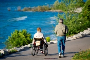 woman in wheelchair and man walking on trail along lakeshore