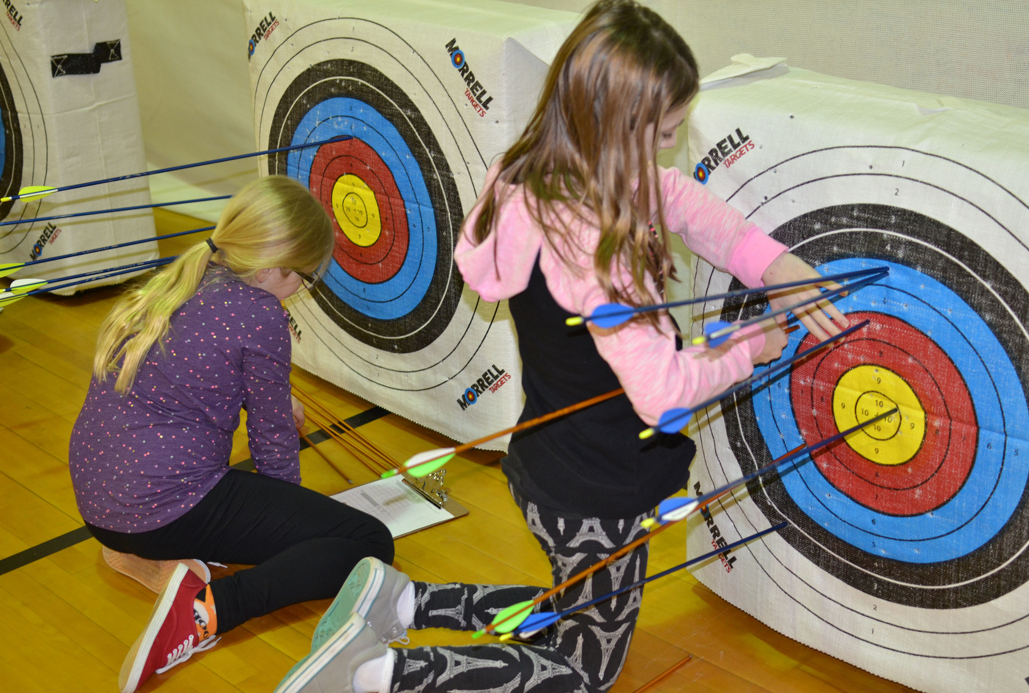 Cherry Creek Elementary School archers check their scores and pull their arrows.
