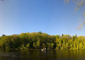 angler on boat on river in Michigan in spring