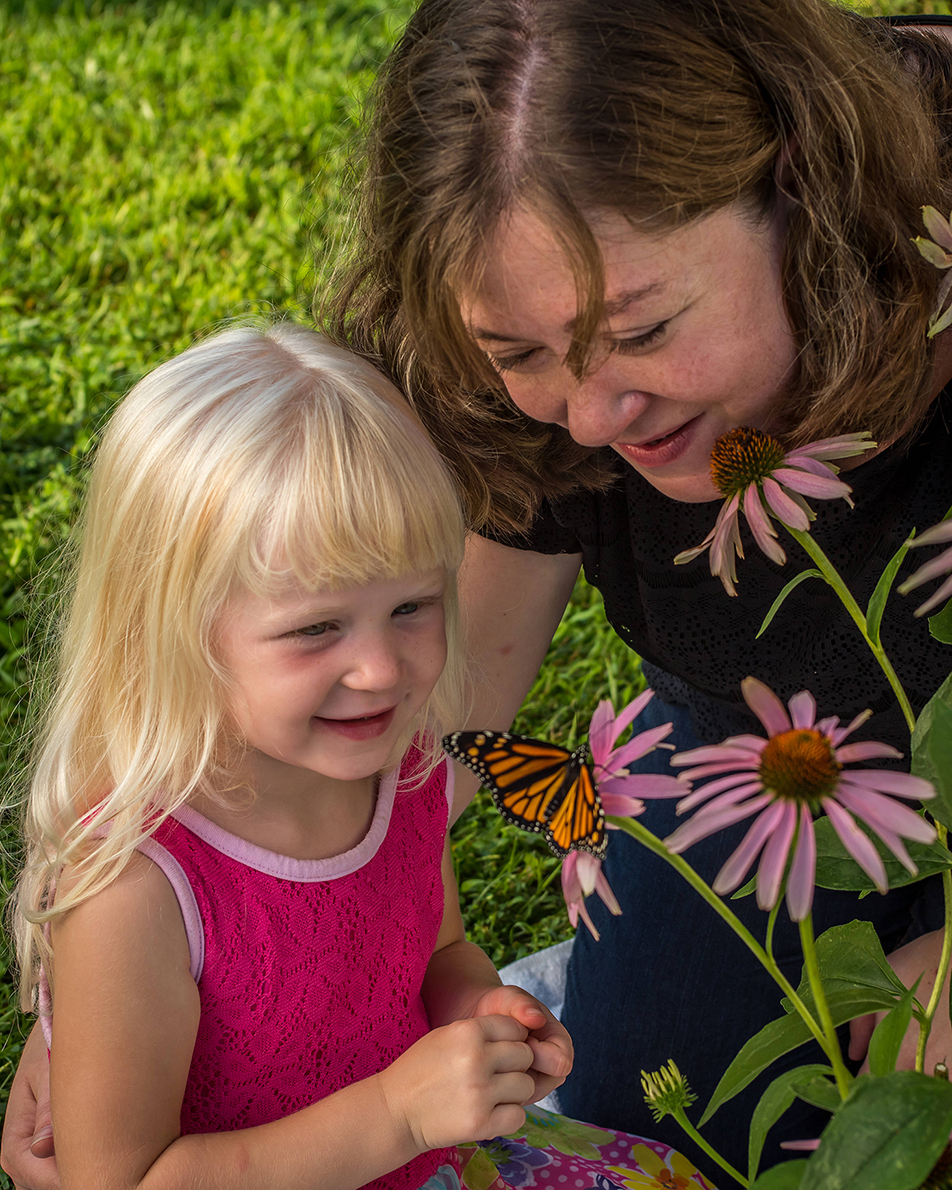 A mother and daughter enjoy looking at a monarch butterfly on a flower. (U.S. Fish and Wildlife Service photo)