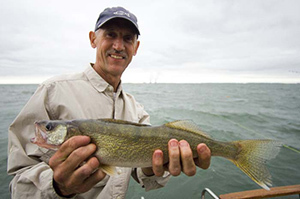 Man holding walleye while on a boat