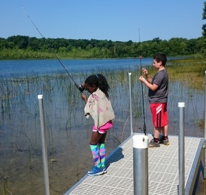 boy and girl fishing from dock