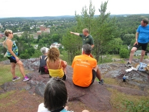 Man in DNR shirt points out sights to group sitting on rock overlooking town