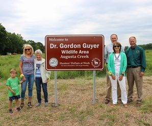 DNR Director Keith Creagh and Guyer's family pose by Dr. Gordon Guyer Augusta Creek Wildlife Area sign