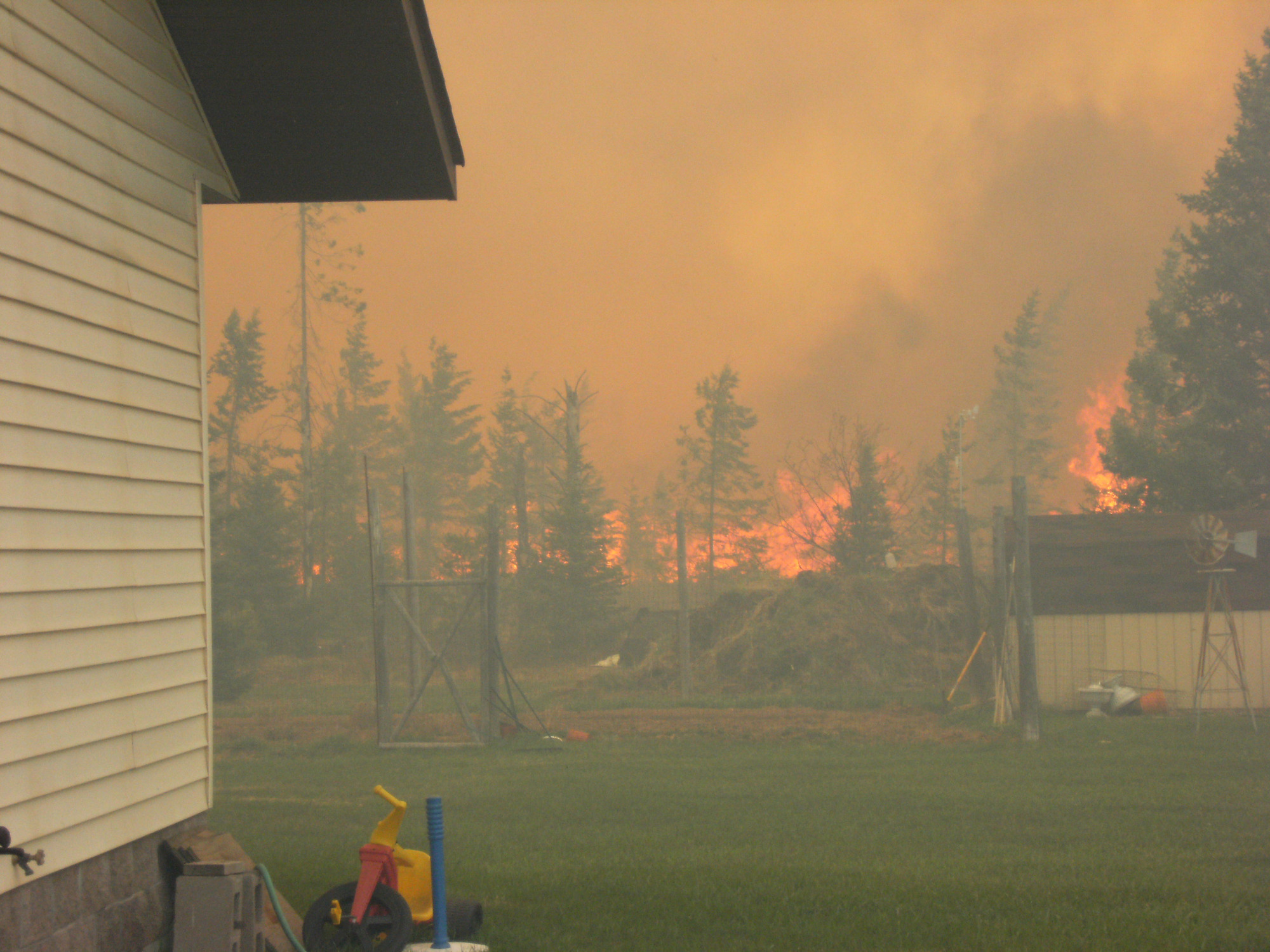 The Black River Falls Fire rages just beyond the backyard of a home in Ely Township in Marquette County.