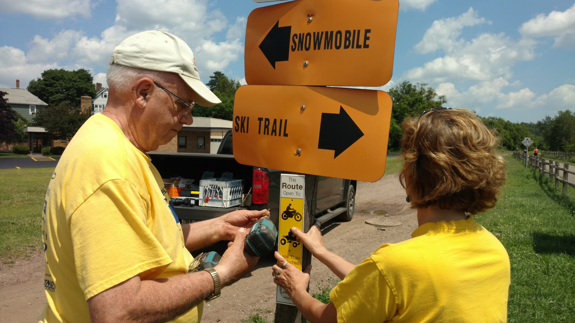 Workers put up signs along a trail section maintained by the Iron Ore Heritage Recreation Authority in Marquette County.