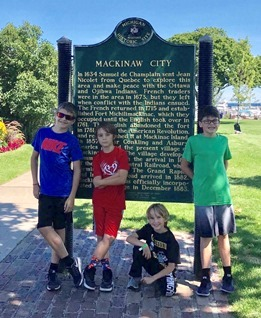 four young boys standing in front of Mackinaw Island historical marker