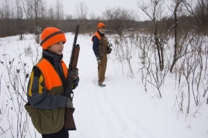 young hunter holding rifle in snowy field with man in background
