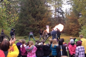 School group watches as flame shoots from cannon during re-enactor demonstration