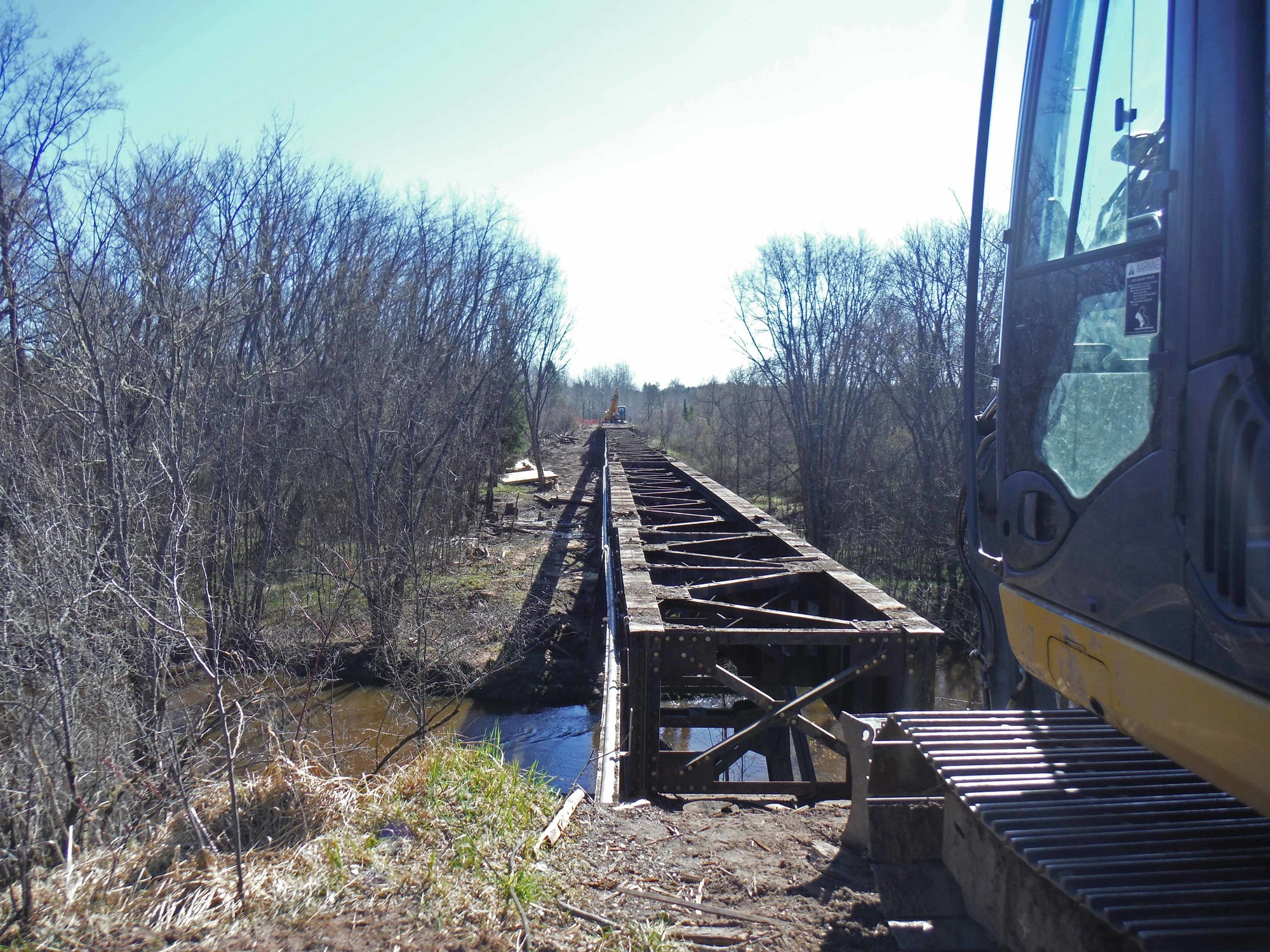 The decking and abutments of a trail bridge over the South Branch of the Ontonagon River are being removed.