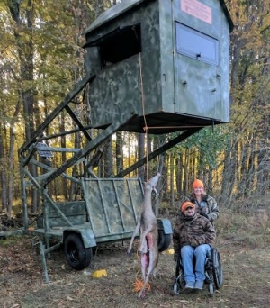Hunter in wheelchair next to harvested deer and accessible hunting blind