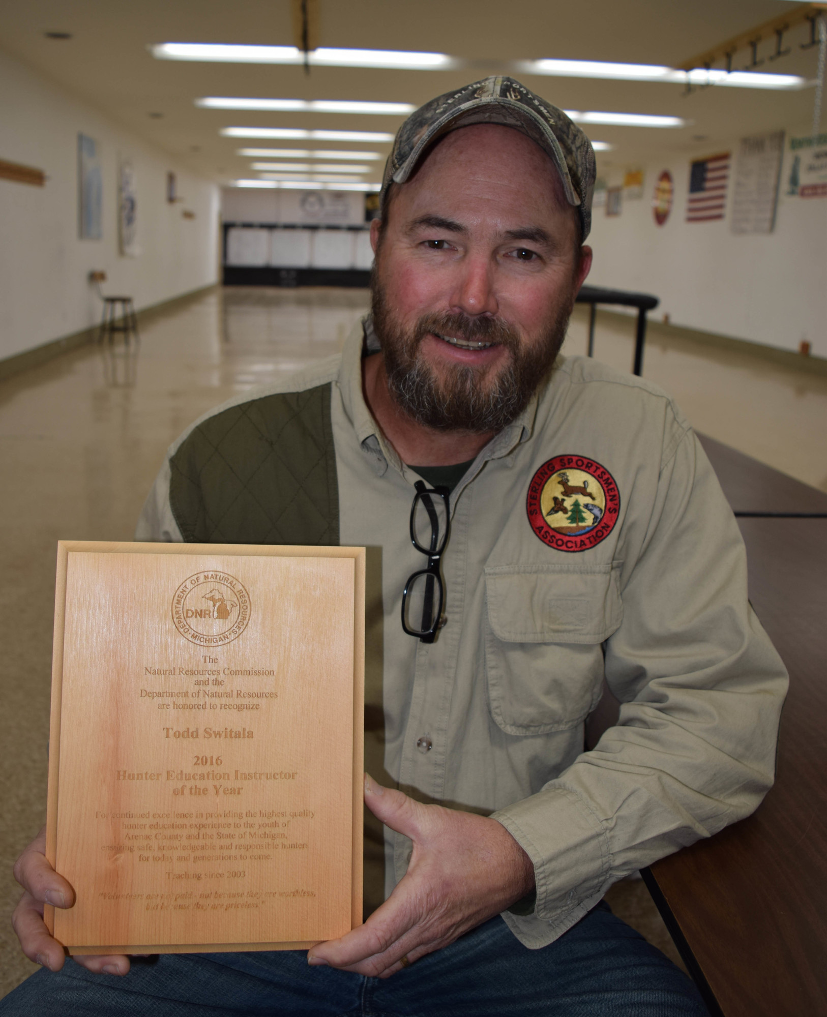 Todd Switala, 2016 Hunter Safety Instructor of the Year displays a plaque recognizing his service.