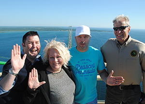 DNR, Yooper Shirts and Peninsulas shake hands on the Mackinac Bridge.