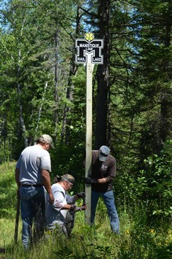 workers installing Haywire Grade mile marker