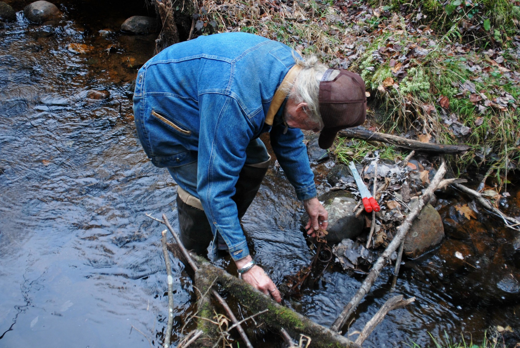 Late trapping legend Johnny Thorpe works to set a trap in a stream.