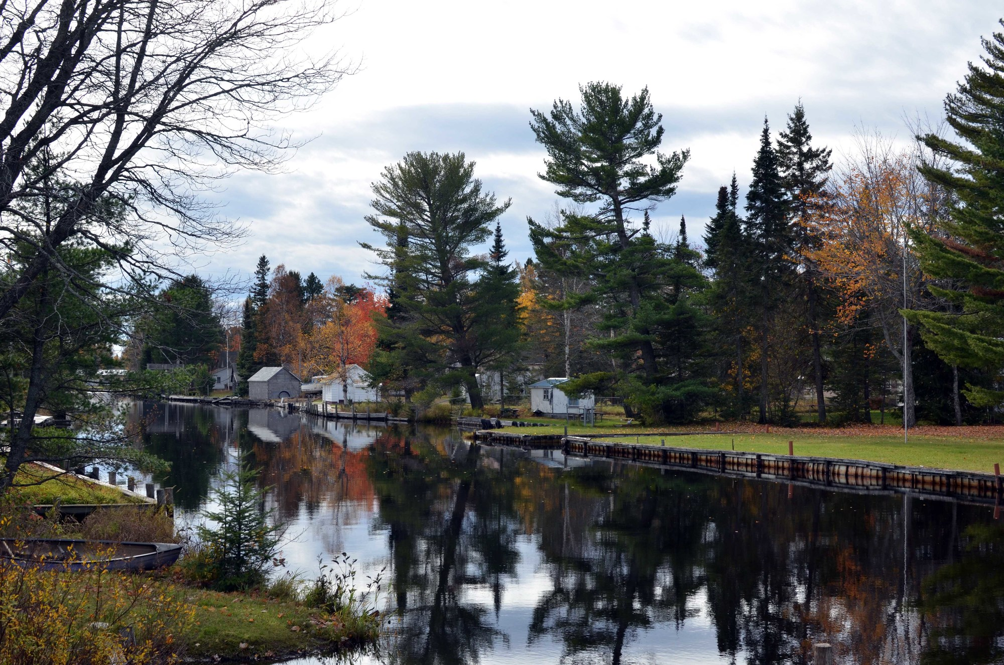 The Big Tamarack River winds slowly toward the Grand Traverse Harbor, past homes, docks and yards.