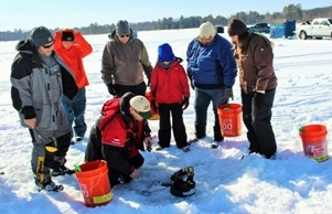 group of people in winter attire surrounding a fishing hole on the ice