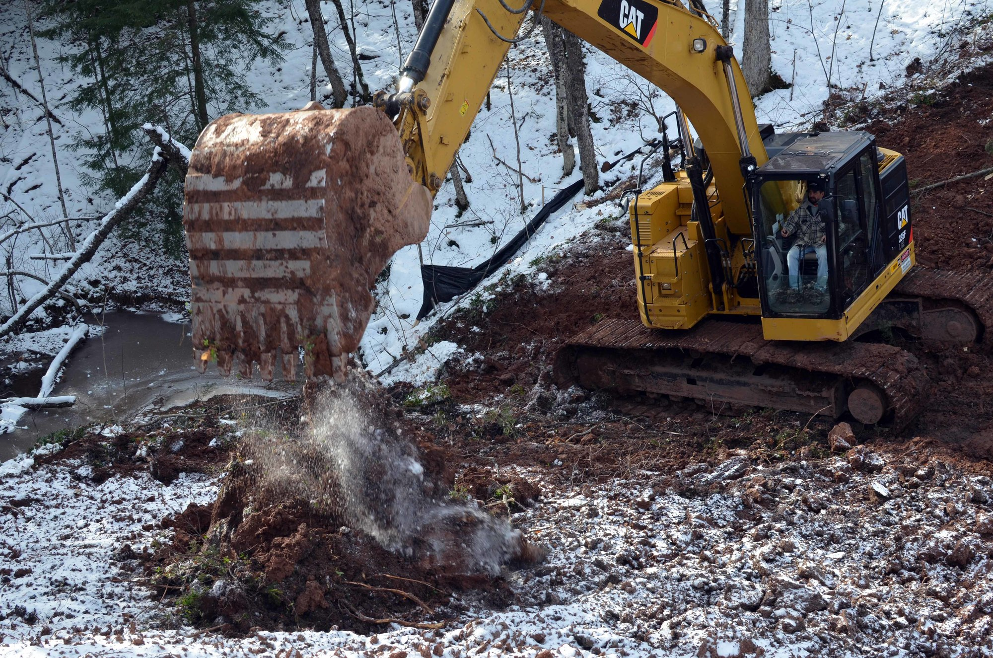 A backhoe operator removes dirt covering the old culvert. (Photo courtesy Don Helsel, MI-TRALE)