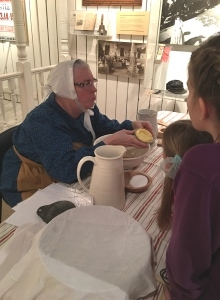 costumed interpreter demonstrates butter making while children look on