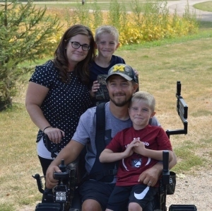 Corey Lantz, in tracked wheelchair, with wife and two sons