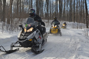 Snowmobilers move along Trail No. 11 South on a sunny day in Gogebic County.