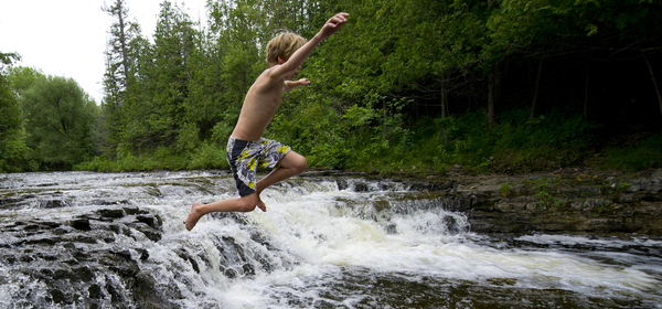 A child jumping into the pool at Ocqueoc falls