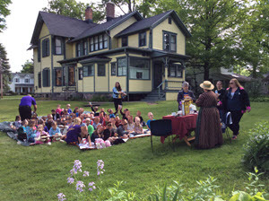 A group of children sit on the Mann House lawn during a program