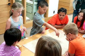 A group of 6 students gather around a table to examine a historic map
