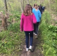 Children walk through the woods with a guide learning about nature