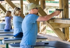 two women and a main target shooting at a shooting range