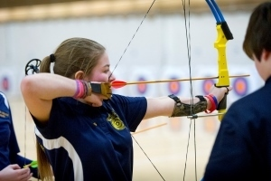 young lady shooting bow and arrow