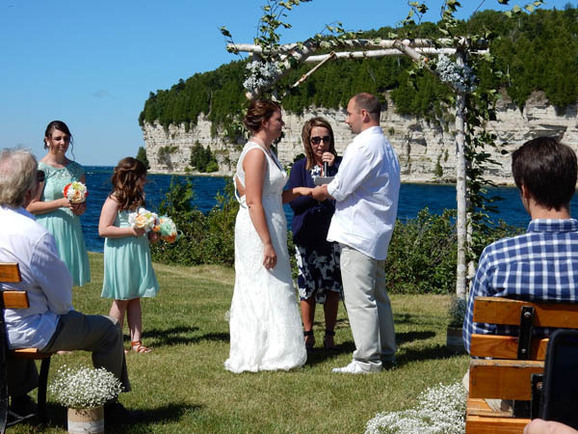 A couple exchanges vows on the Lake Michigan shoreline at Fayette Historic State Park in Delta County
