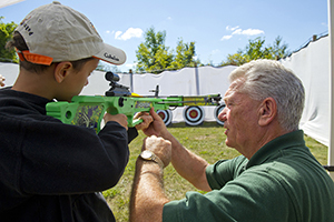 DNR staffer helping boy shoot crossbow at target