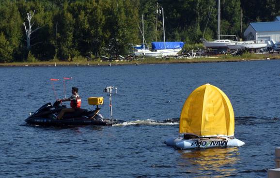 A modified jet ski cruises past an autonomous buoy that is holding station.