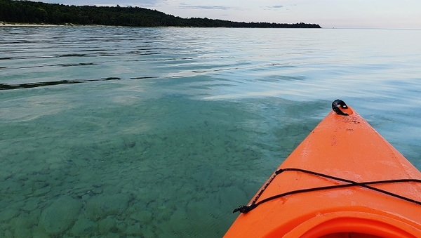 The tip of an orange kayak cuts into the Lake Michigan waters of the Beaver Island water trail