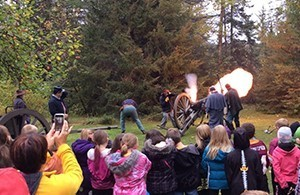 kids watch costumed Civil War re-enactors fire canon
