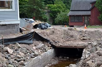 A house lies in direct line of stones from a creek had the culvert plugged and flooded.