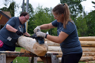 Mark and Corrina Kostrzewa of Jackson work on preparing a fence post for the stockade at Fort Wilkins.
