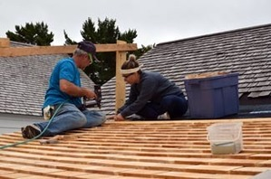 Volunteers work to resurface a roof at Fort Wilkins.