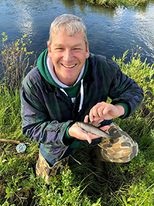 Man holding Arctic grayling next to stream