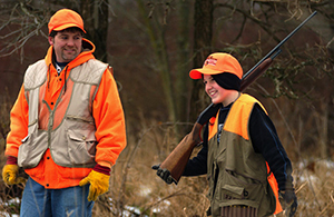 man and boy in hunting clothes, boy holding hunting rifle