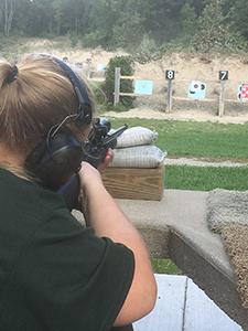 DNR staffer Makenzie Schroeder shooting a rifle at a target