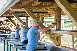 man and two women target shooting with handguns at shooting range