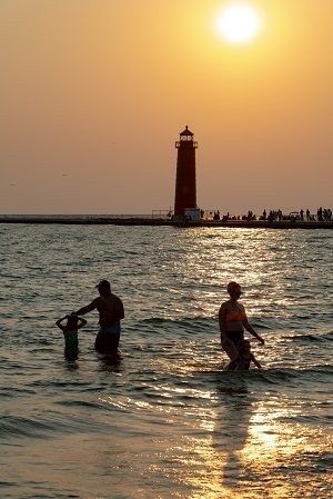 A family enjoying the water on the beach at Grand Haven State Park