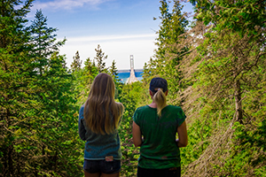 two women looking at view of Mackinac Bridge through forest opening